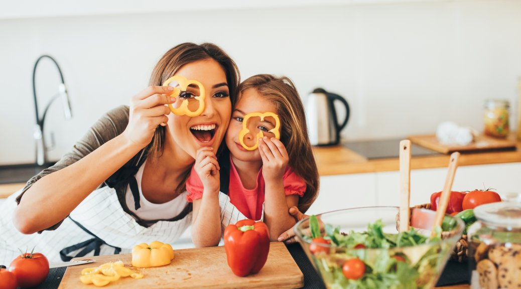 Happy mother and daughter having fun while making easy weeknight recipes in the kitchen.